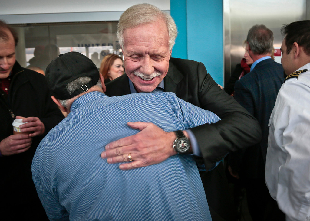 """. Captain Chesley \""""Sully\"""" Sullenberger III, center, pilot of U.S. Airways Flight 1549, hugs Louis Salerno, a senior deck hand with N.Y. Water ways ferry, on Wednesday, Jan. 15, 2014 in New York.  Salerno rescued Sullenberger after the Captain safely glided Flight 1549 with 155 passengers and crew to a water landing.  Sullenberger gathered with some survivors and rescuers to mark the fifth anniversary of the event known as the \""""miracle on the Hudson.\"""" (AP Photo/Bebeto Matthews)"""