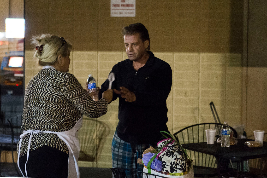 . Nicolette Wingert, left, gives out water to a homeless man outside a doughnut shop in Glendora on Wednesday night, Nov. 27, 2013. Nicolette Wingert has been feeding the homeless six days a week for the past seven years with Nurses4Christ, a nonprofit organization she founded in 2006. She and Phillip Stern of Glendora have been going every day since 2008, feeding homeless people sandwiches and hot food; giving them bottles of water, clothes and blankets. (Photo by Watchara Phomicinda/San Gabriel Valley Tribune)