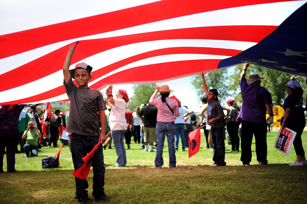 ". People hold up an American flag at the ""Caravan for Citizenship\"" rally at Yokuts Park in Bakersfield, Wednesday, August 14, 2013. (Michael Owen Baker/L.A. Daily News)"