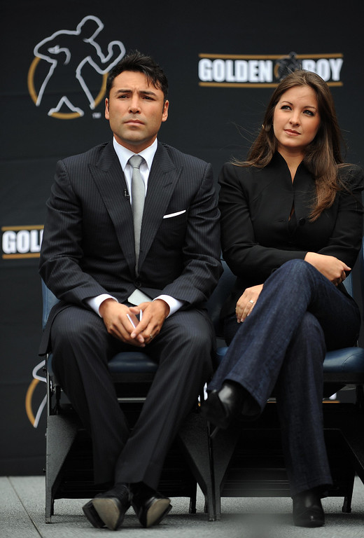""". Oscar De La Hoya and his wife Millie Corretjer listen to Los Angeles Mayor Antonio Villaraigosa (out of frame) after De La Hoya announced his retirement from boxing at a press conference in Los Angeles on April 14, 2009. The 10-time boxing world champion, \""""Golden Boy\"""" De la Hoya\'s last bout was back in December when Filipino Manny Pacquiao easily stopped him in the eighth round.   (GABRIEL BOUYS/AFP/Getty Images)"""