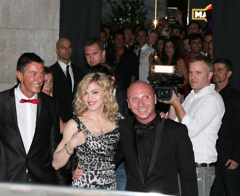 ". U.S singer Madonna between Italian stylists Stefano Gabbana, left, and Domenico Dolce, right, at the entrance of their ""Gold\"" restaurant in Milan where she attended a party after her concert, part of her Sticky and Sweet tour, at the San Siro stadium in Milan, Italy, Tuesday night, July 14, 2009. (AP Photo/Tommaso Balestra)"