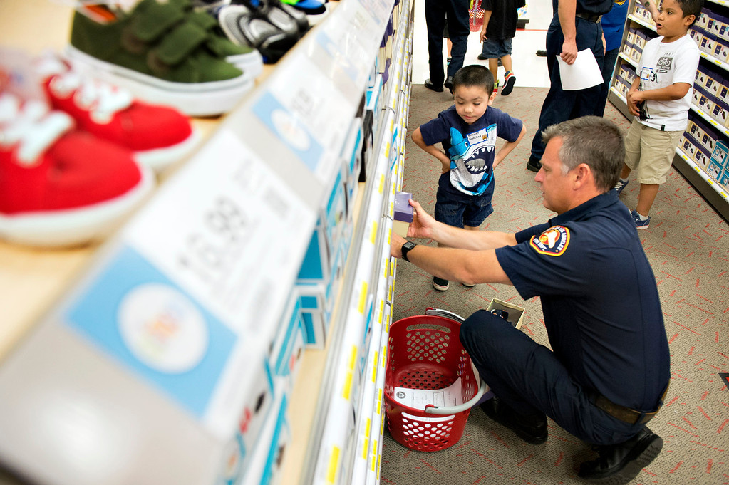 . Volunteers from the Soroptimists club, as well as the RSVP (retired senior volunteer patrol) of La Verne PD, Los Angeles County Sheriff\'s Department and Los County firefighters all paired up with a student from Bonita Unified elementary to take them shopping and find clothes and shoes at Target in San Dimas on Tuesday, Sept. 10, 2013. (Photo by Watchara Phomicinda/ San Gabriel Valley Tribune)