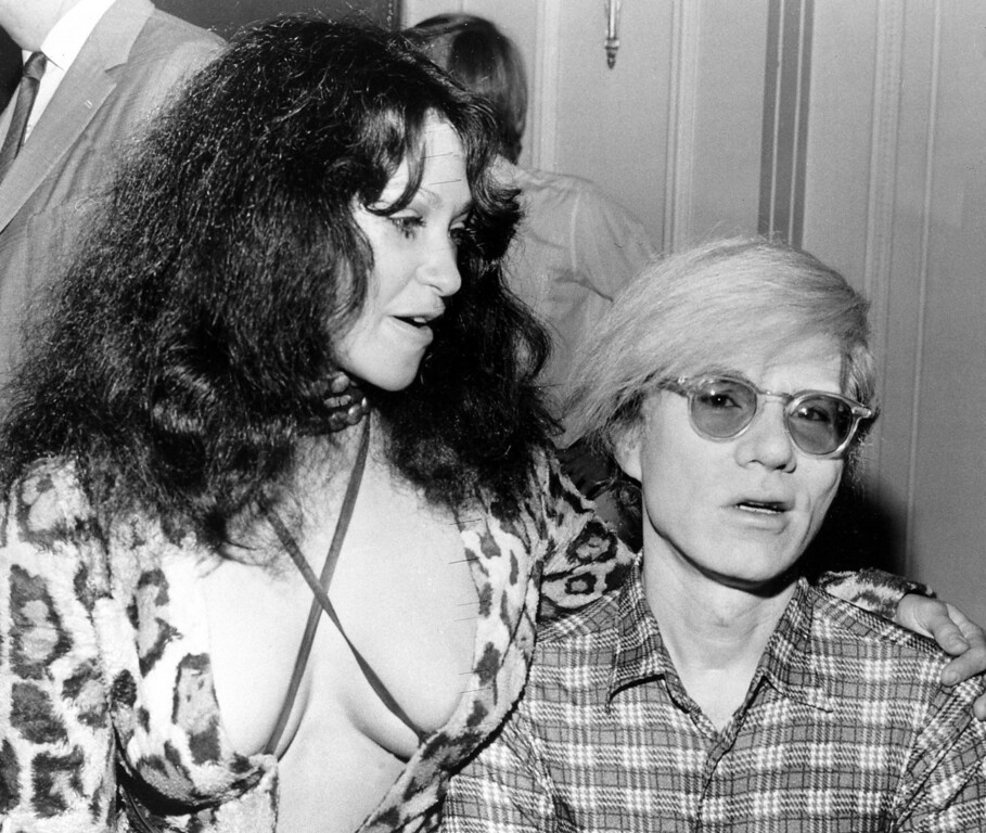 ". American pop artist Andy Warhol, right, is shown with Geri Miller, who plays Josie in his play ""Pork,\"" at a news conference at the Ritz Hotel in London, England, on Aug. 2, 1971.  (AP Photo)"