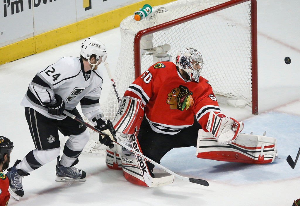 . Chicago Blackhawks goalie Corey Crawford (50) defects a shot by Los Angeles Kings center Colin Fraser (24) during the second period in Game 1 of the NHL hockey Stanley Cup Western Conference finals Saturday, June 1, 2013, in Chicago. (AP Photo/Charles Rex Arbogast)
