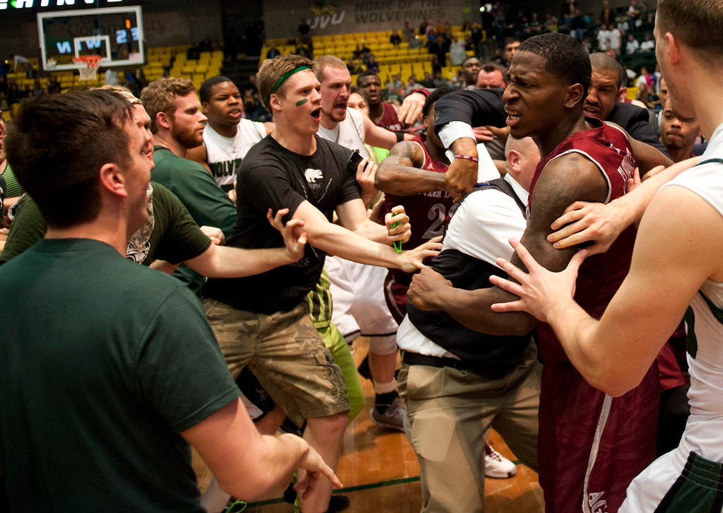 . In this Thursday, Feb. 27, 2014 photo, New Mexico State\'s DK Eldridge, at right in red and white uniform, is held by security during  a brawl involving players and fans who came onto the court when New Mexico State guard K.C. Ross-Miller hurled the ball at Utah Valley\'s Holton Hunsaker seconds after the Wolverines\' 66-61 overtime victory against the Aggies.  (AP Photo/The Daily Herald, Grant Hindsley)