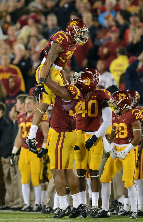 . USC�s Su\'a Cravens #21 is lifted in the air by Leonard Williams #94 after he incepted a Stanford pass in the fourth quarter during their game at the Los Angeles Memorial Coliseum Saturday, November 16, 2013. USC beat Stanford 20-17. (Photos by Hans Gutknecht/Los Angeles Daily News)