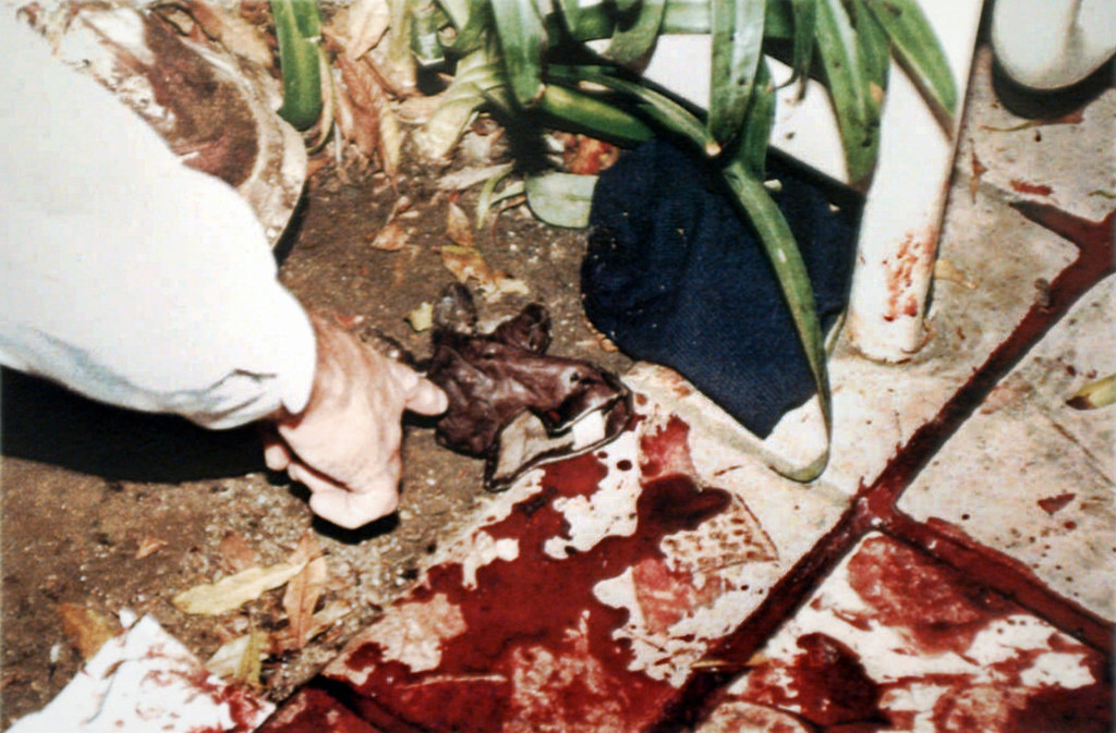 . Former Los Angeles Police Department Detective Mark Fuhrman is seen pointing to a glove found near the bloodstained walkway of Nicole Brown Simpson\'s Bundy Drive condominium as seen in this LAPD evidence photo, introduced and accepted as evidence and released for publication, in the O.J. Simpson wrongful-death civil trial Monday, Oct. 28, 1996, in Superior Court in Santa Monica, Calif.  (AP Photo/LAPD)