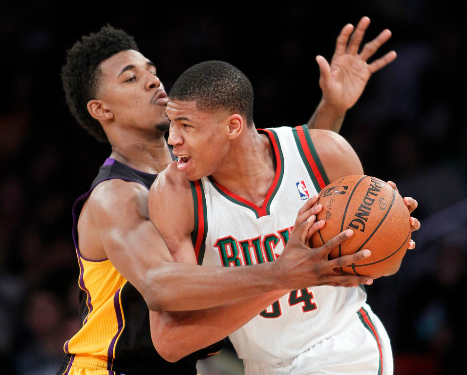 . Los Angeles Lakers forward Nick Young, left, reaches for the ball against Milwaukee Bucks shooting guard Giannis Antetokounmpo during the first half of an NBA basketball game Tuesday, Dec. 31, 2013, in Los Angeles. (AP Photo/Alex Gallardo)