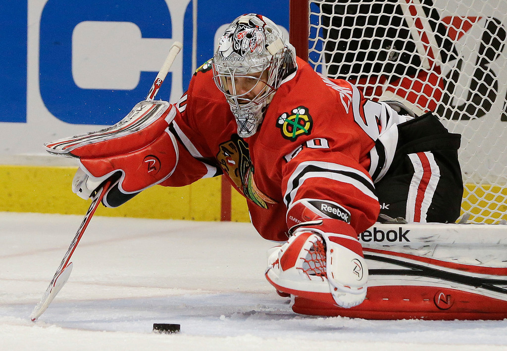 . Chicago Blackhawks goalie Corey Crawford (50) reaches to smother the puck against the Los Angeles Kings during the third period of Game 2 of an NHL hockey Stanley Cup Western Conference finals, Sunday, June 2, 2013, in Chicago. Chicago won 4-2. (AP Photo/Nam Y. Huh)