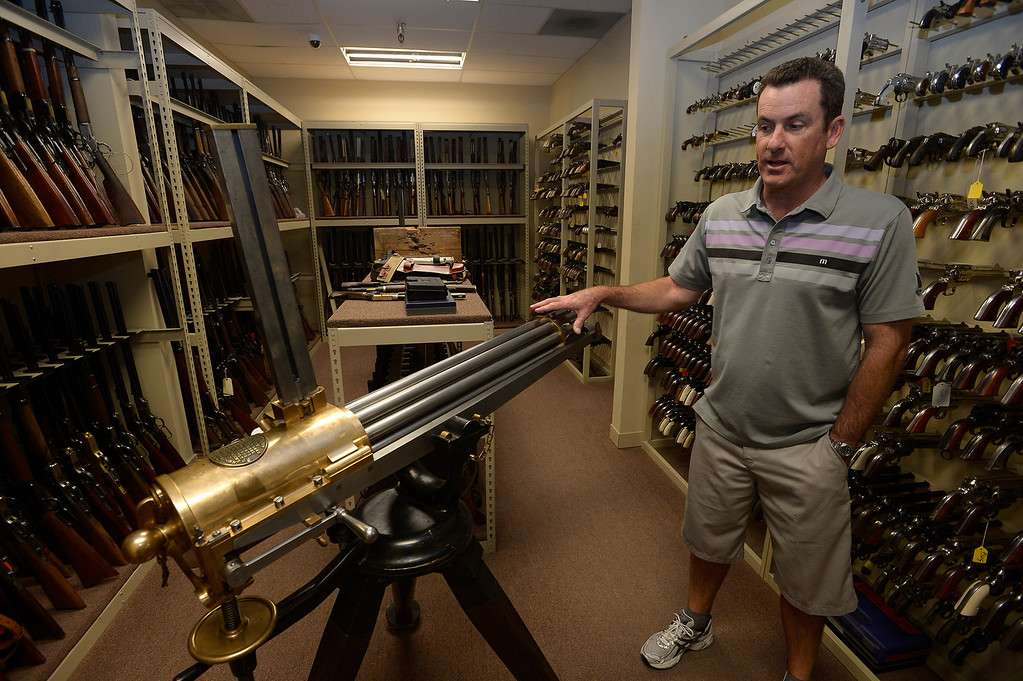 . Gregg Bilson, Jr. looks at a 1800\'s vintage gatling gun. Bilson is the CEO of ISS Independent Studio Services, a prop house that holds hundreds of thousands of items used for motion pictures and television production. Runaway production has an impact on his business. Sunland, CA 12-31-2013. photo by (John McCoy/Los Angeles Daily News)