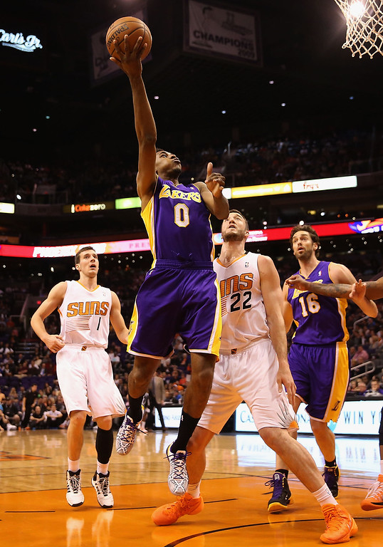 . Nick Young #0 of the Los Angeles Lakers puts up a shot past Miles Plumlee #22 of the Phoenix Suns during the first half of the NBA game at US Airways Center on January 15, 2014 in Phoenix, Arizona.    (Photo by Christian Petersen/Getty Images)