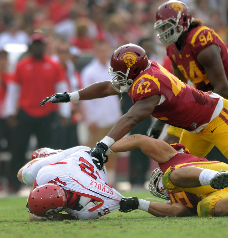 . USC\'s J.R. Tavai and Devon Kennard (#42) sack Utah QB Adam Schulz in the fourth quarter, Saturday, October 26, 2013, at the L.A. Memorial Coliseum. (Michael Owen Baker/L.A. Daily News)