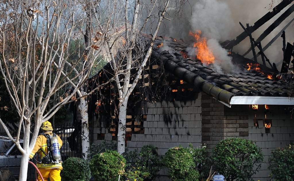 . Los Angeles County Firefighters battle a fire in the garage area that damaged a single family home. The fire started in the garage along the 1300 block of Via Verde. No injuries, but 5 cars were destroyed including two jaguars in San Dimas, Calif., on Saturday, Jan.4, 2014.   (Keith Birmingham Pasadena Star-News)