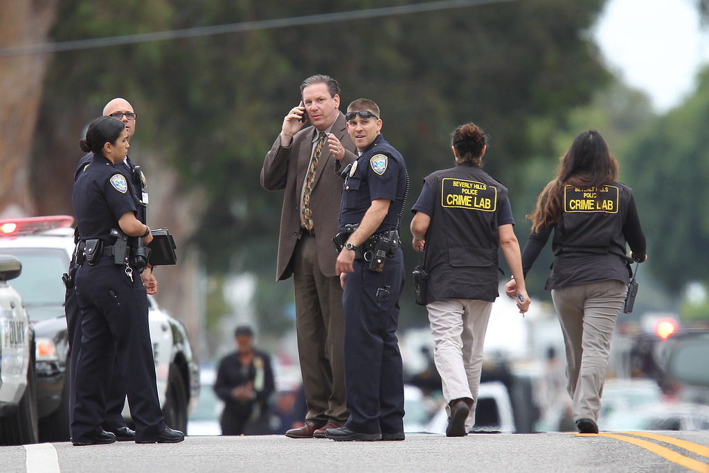 . SANTA MONICA, CA - JUNE 07:  Investigators look around near the scene of two shooting fatalities and a possible suspicious package after multiple shootings took place at various locations including Santa Monica College June 7, 2013 in Santa Monica, California. According to reports, at least six people have died in the shootings.  (Photo by David McNew/Getty Images)