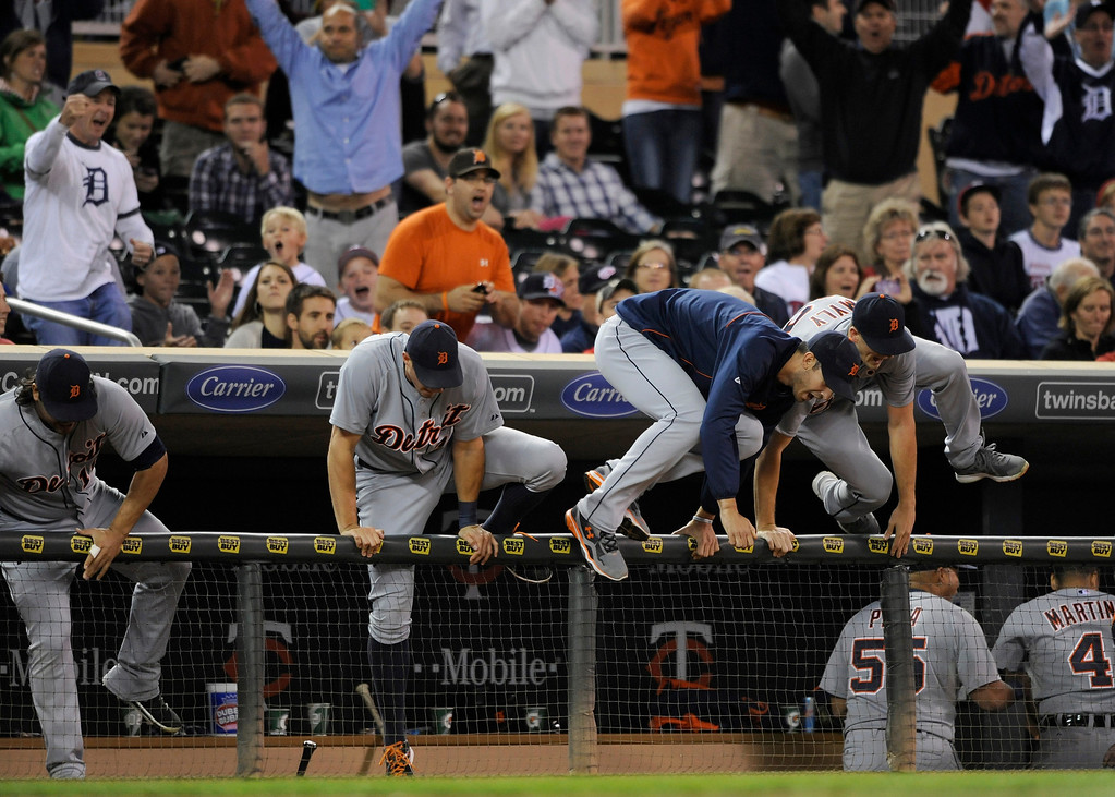. MINNEAPOLIS, MN - SEPTEMBER 25: (L-R) Matt Tuiasosopo #18, Don Kelly #32, Rick Porcello #21 and Drew Smyly #33 of the Detroit Tigers jump out of the dugout after a win of the game against the Minnesota Twins on September 25, 2013 at Target Field in Minneapolis, Minnesota. The Tigers clinched the American League Central Division title with a 1-0 win over the Twins. (Photo by Hannah Foslien/Getty Images)