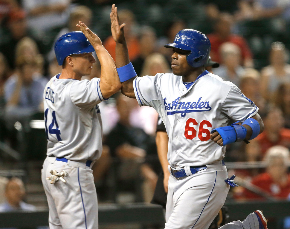 . Los Angeles Dodgers\' Yasiel Puig (66) and Mark Ellis high-five after scoring on a double by  Hanley Ramirez during the fifth inning of a baseball game against the Arizona Diamondbacks, Wednesday, July 10, 2013, in Phoenix. (AP Photo/Matt York)