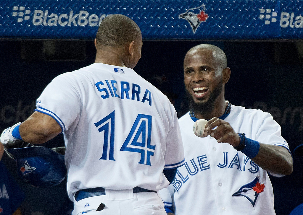 . Toronto Blue Jay\'Jose Reyes, right, gives teammate Moises Sierra, left, his at-bat ball after Sierra hit a triple and then advanced to home plate to score a run after there was an error at third base while playing against the Los Angeles Angels during fourth-inning AL baseball game action in Toronto, Wednesday, Sept. 11, 2013. (AP Photo/The Canadian Press, Nathan Denette)