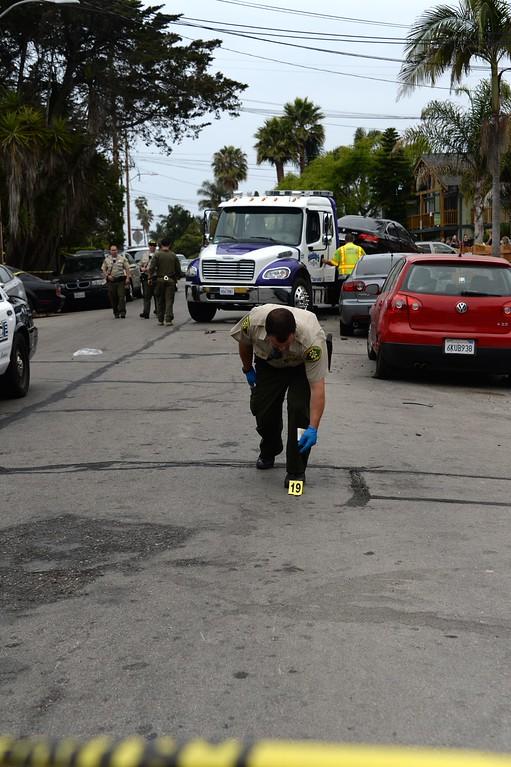 ". A police officer marks evidence on May 24, 2014, after a drive-by shooting in Isla Vista, California, a beach community next to the University of California Santa Barbara. Seven people, including the gunman, were killed and seven others wounded in the May 23 mass shooting, Santa Barbara County Sheriff Bill Brown said Saturday. Brown said at a pre-dawn press conference that the shooting in the town of Isla Vista ""appears to be a mass murder situation.\"" Driving a black BMW, the suspect opened fire on pedestrians from his vehicle at several locations in the town.            (ROBYN BECK/AFP/Getty Images)"