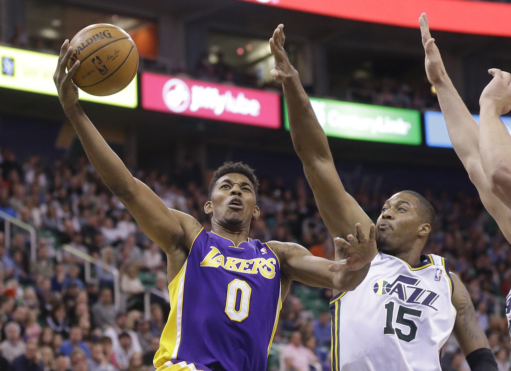 . Los Angeles Nick Young (0) lays the ball as Utah Jazz\'s center Derrick Favors (15) defends in the second quarter during an NBA basketball game Monday, April 14, 2014, in Salt Lake City, Utah. (AP Photo/Rick Bowmer)