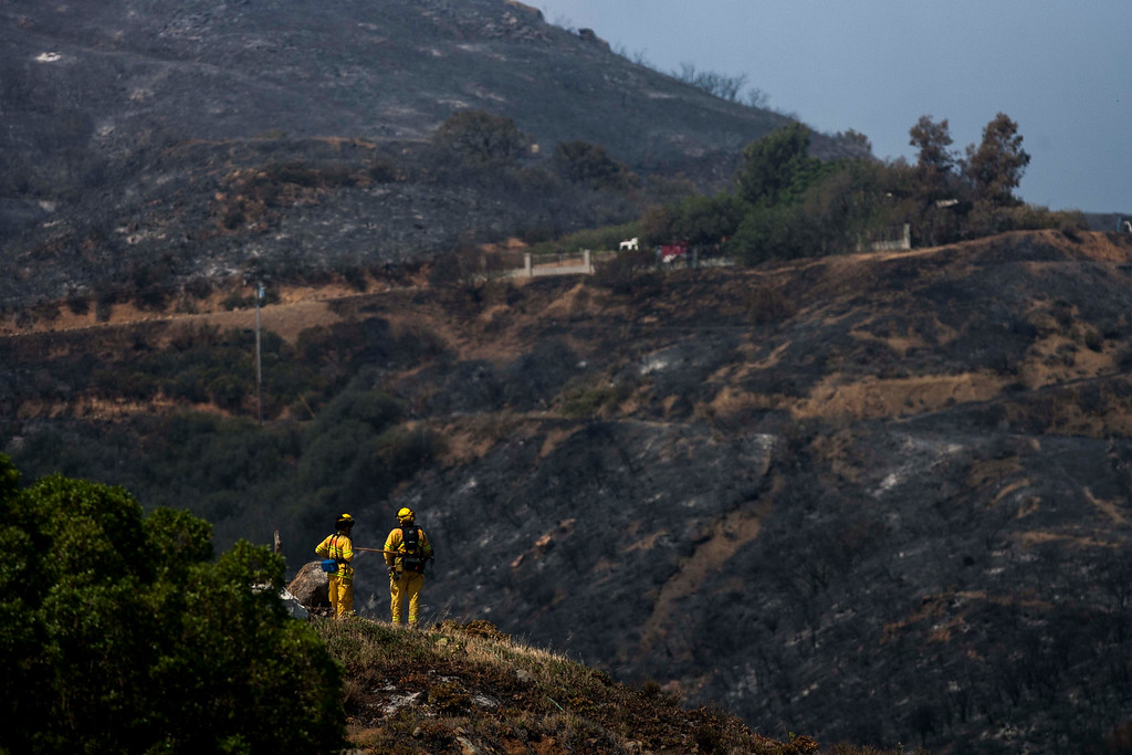 . Firefighters keep watch after a wildfire around the burnt area near Point Mugu, Calif., Saturday, May 4, 2013.  High winds and withering hot, dry air was replaced by the normal flow of damp air off the Pacific, significantly reducing fire activity.  (AP Photo/Ringo H.W. Chiu)