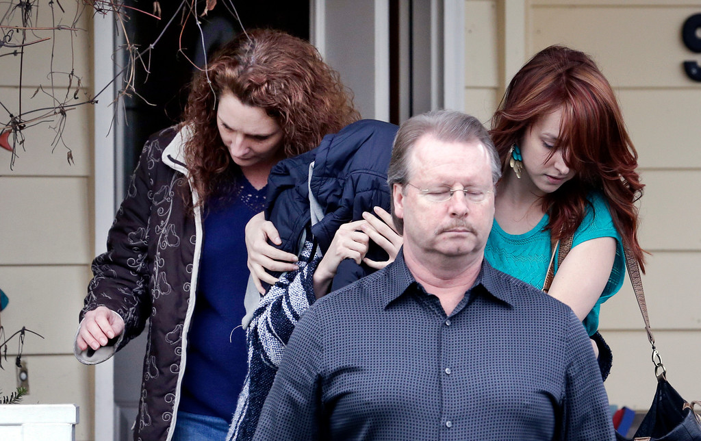 ". A woman believed to be Amanda Knox, center left, is hidden under a jacket while being escorted from her mother\'s home to a car by family members Thursday, Jan. 30, 2014, in Seattle. Amanda Knox says she is frightened and saddened by her ""unjust\"" murder conviction in the death of her British roommate Meredith Kercher. Knox\'s lawyers have vowed to appeal to Italy\'s highest court. In a statement issued from Seattle on Thursday after her conviction was upheld, Knox blamed overzealous prosecutors and a \""prejudiced and narrow-minded investigation\"" for what she called a perversion of justice and wrongful conviction. (AP Photo)"
