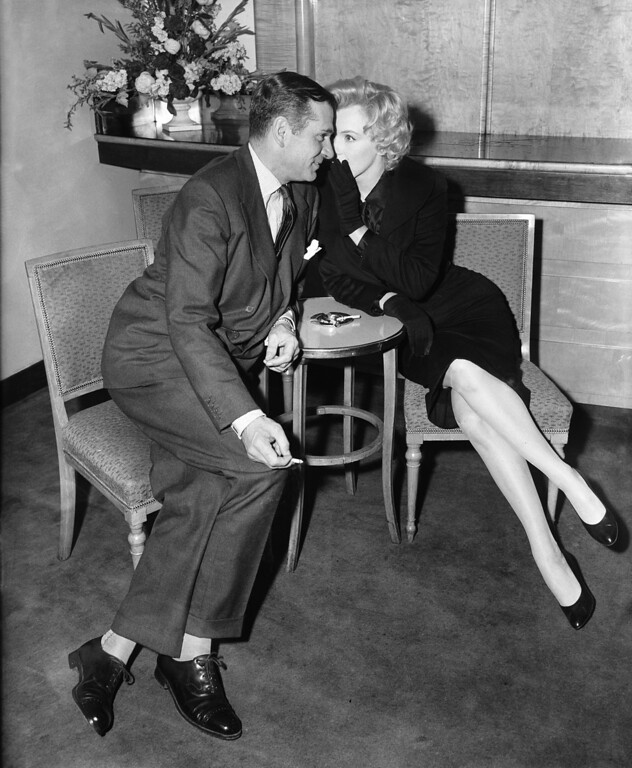 . American actress Marilyn Monroe (1926 - 1962) whispers to English actor and director Laurence Olivier (1907 - 1989) during a press conference at the Savoy Hotel, London, 16th July 1956. Monroe is in England to co star with Olivier in the \'The Prince and the Showgirl\'. (Photo by Central Press/Hulton Archive/Getty Images)
