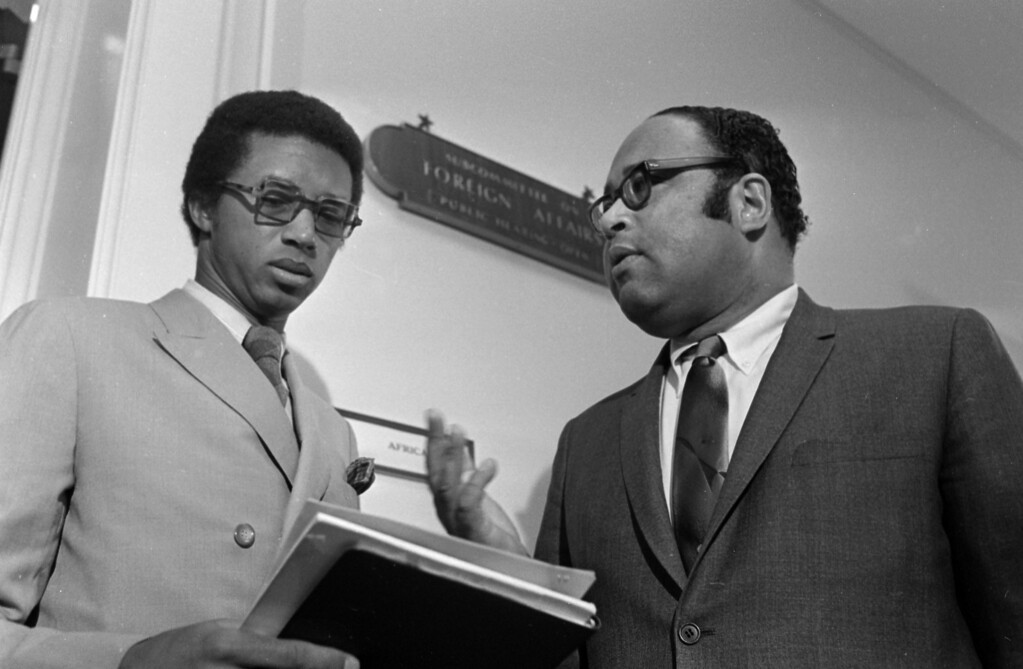 """. Tennis star Arthur Ashe of Richmond, Va., left, talks with Chairman Charles C. Diggs, D-Michigan, of the House Foreign Affairs subcommittee on Africa, Feb. 4, 1970.  Ashe was denied a visa by South Africa, compelling hearings \""""to probe the foreign implications of a black American having his visa denied,\"""" said Diggs.  (AP Photo/Bob Daugherty)"""