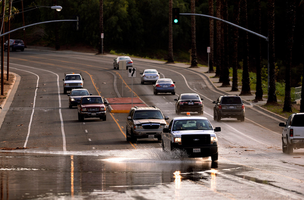 . Traffic flows through a flooded section of the 5100 block of Palm Avenue  in Riverside August 29, 2013. GABRIEL LUIS ACOSTA/STAFF PHOTOGRAPHER.