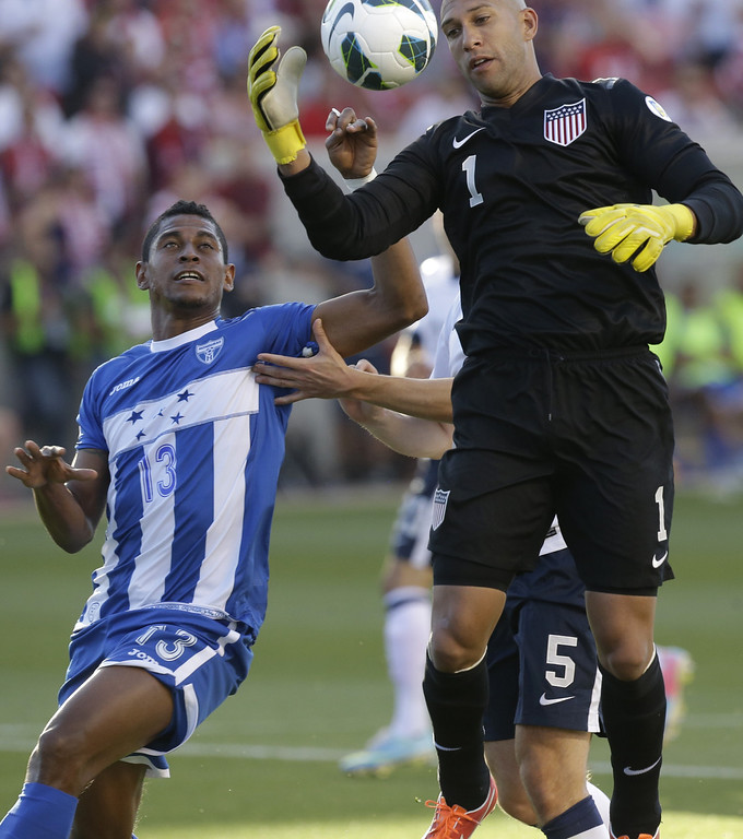 . United States goalie Tim Howard (1) grabs the ball as Honduras\' Carlo Costly (13) looks on in the first half during an World Cup qualifying soccer match at Rio Tinto Stadium on Tuesday, June 18, 2013, in Sandy, Utah.  (AP Photo/Rick Bowmer)