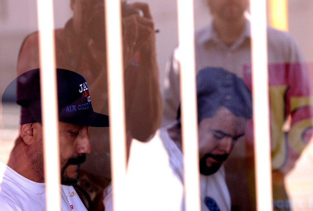 . Co-owners Jerry Lopez, 38, left, of San Bernardino, and Tomas Dominic Castro, 37, right, of Highland, are detained by San Bernardino Police as they conduct a raid at a marijuana dispensary along the 3200 block of North E Street in San Bernardino May 9, 2013. GABRIEL LUIS ACOSTA/STAFF PHOTOGRAPHER.