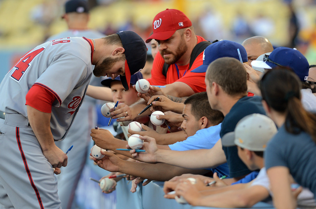 . Bryce Harper of the Washington Nationals signs autographs prior to the start of game one of a three game series against the Dodgers in Los Angeles, CA May 13, 2013.(Andy Holzman/Staff Photographer)
