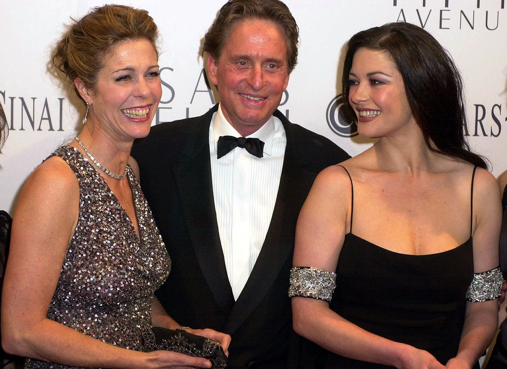 ". Actress Rita Wilson, left, actor Michael Douglas and his wife, Catherine Zeta-Jones, right, share a laugh prior to the 5th Annual ""An Unforgettable Evening\"" gala at the Regent Beverly Wilshire Hotel in Beverly Hills, Calif., Tuesday, March 27, 2001. The annual fundraising event benefits Cedars-Sinai Research for Women\'s Cancers, underwritten by Saks Fifth Avenue. (AP Photo/Michael Caulfield)"