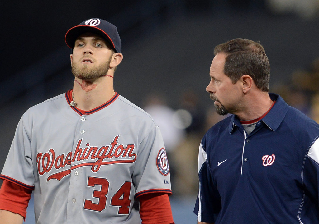 . Bryce Harper of the Washington Nationals is walked off the field by Nationals head athletic trainer Lee Kuntz during the 5th inning againt the Dodgers May 13, 2013 in Los Angeles, CA.  Harper crashed into the right field wall while trying to catch a hit by Dodgers A.J. Ellis.  Harper needed 11 stitches to close a wound received during the play.(Andy Holzman/Staff Photographer)