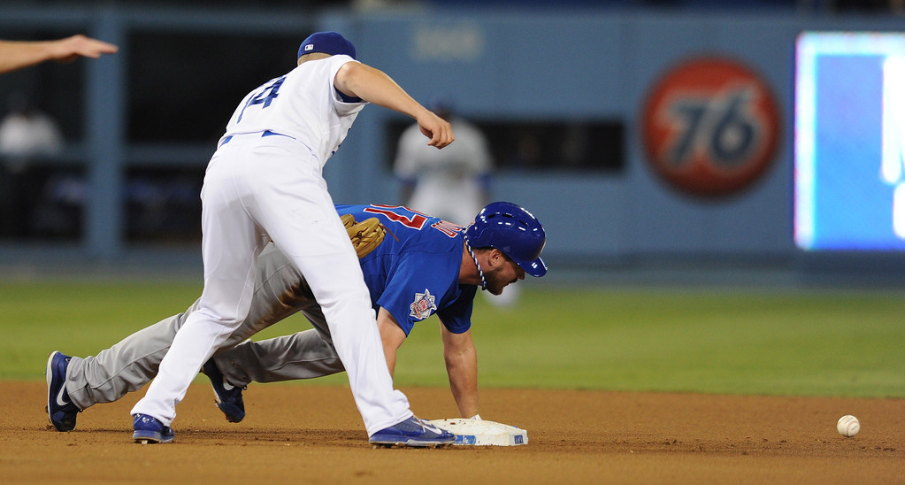 . Los Angeles Dodgers second baseman Mark Ellis, right, drops the ball as Chicago Cubs\' Travis Wood dives back to second during the third inning. The Cubs were in town to play the Dodgers. Los Angeles, CA. 8/24/2013(John McCoy/LA Daily News)