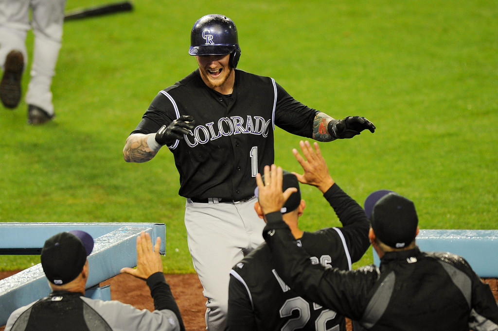 . The Rockies\' Brandon Barnes is greeted at the dugout after scoring from second on a hit by Charlie Blackmon in the 11th inning, Friday, April 25, 2014, at Dodger Stadium. (Photo by Michael Owen Baker/L.A. Daily News)