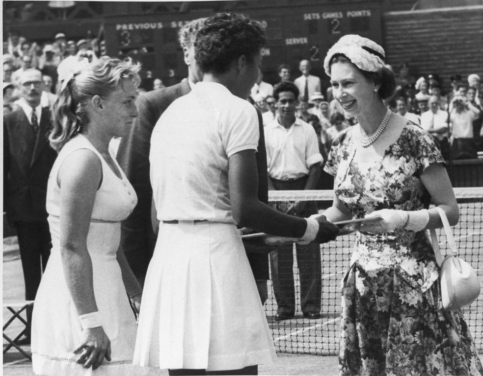 . Queen Elizabeth II of England, right, presents winners trophy to Althea gibson who won the women\'s title in the All England Lawn Tennis Championship at Wimbledon, England, july 6, 1957. Gibson defeated Darlene Hard, left, 6-3, 6-2. (AP Photo)