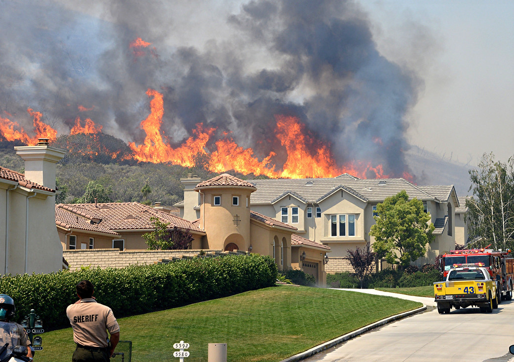 . Firefighters provide structure protection on Via Mira Flores in Thousand Oaks during the Springs fire as flames approach houses. Photo by Rick McClure