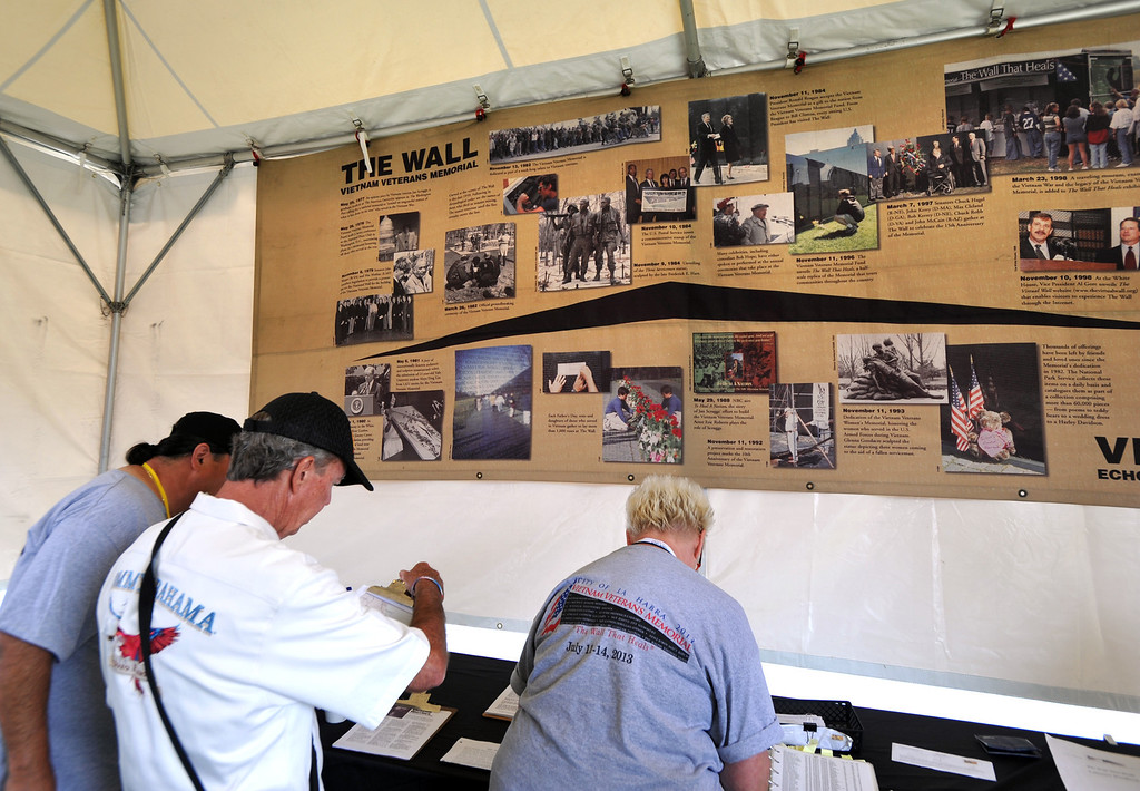 ". Visitors look look up names on the ""Wall that Heals\"" traveling replica of the Vietnam Veterans Memorial wall at La Habra High School in La Habra on Thursday July 11, 2013. The wall will be in the stadium until the closing ceremony on Sunday. (SGVN/Staff Photo by Keith Durflinger)"