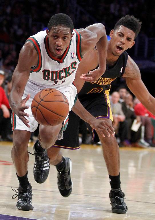 . Milwaukee Bucks guard Brandon Knight, left, drives past Los Angeles Lakers forward Nick Young during the second half of an NBA basketball game Tuesday, Dec. 31, 2013, in Los Angeles. The Bucks won 94-79. (AP Photo/Alex Gallardo)