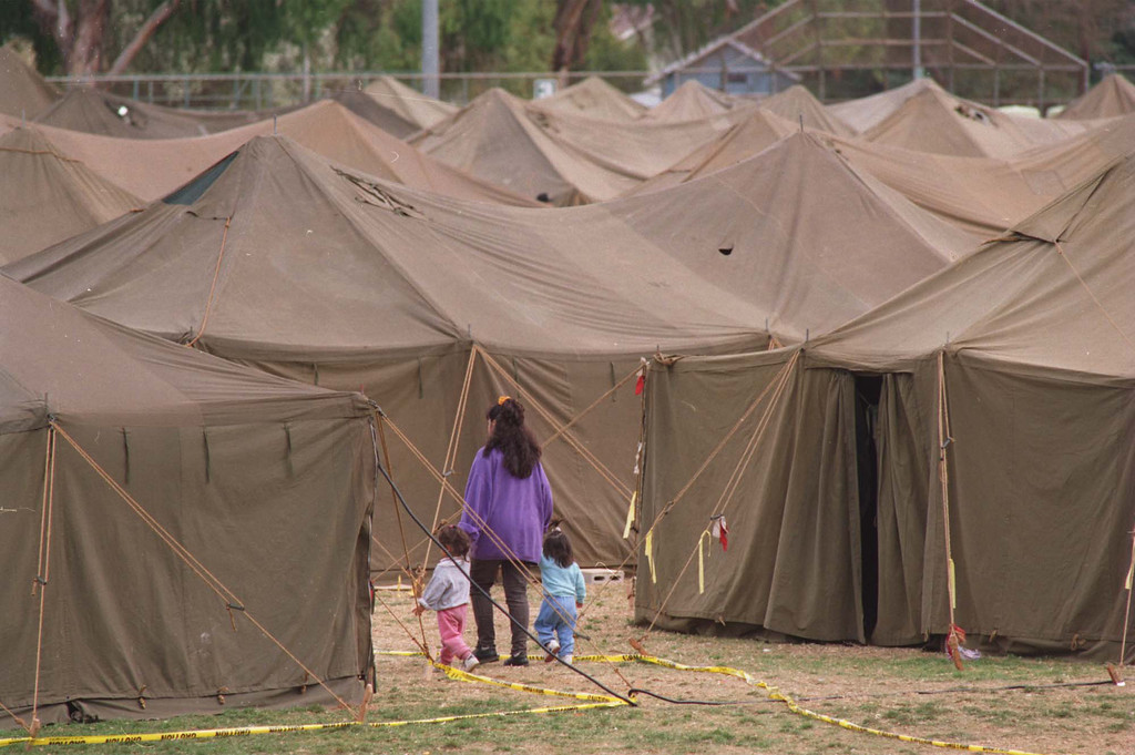 """. A woman leads two children through a maze of tents set up by the National Guard for displaced quake victims at Lanark Park.  The Northridge quake hit at 4:31 the morning of Jan. 17, 1994, a powerful jolt that flattened buildings, destroyed homes, damaged freeways, ignited fires and disrupted water and power.  The 6.7-magnitude Northridge Earthquake also killed nearly three dozen people, injured 8,700 more, caused some $20 billion in damage and shattered the nerves of millions of Southern California residents.  \""""It was like the devil was waking up ... it was a horrifying feeling,\"""" said one of the quake victims quoted in a Daily News story on Jan. 18.  Photo by Michael Owen Baker/Daily News"""