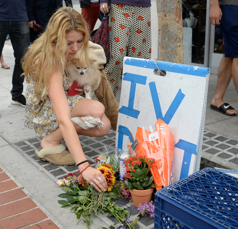 . May 24-,2014. Isla Vista, CA. UCSB student Arrow Denoyer lays down flowers at the sight where one person was killed by the drive-by shooter Friday night. Seven people are dead, including the attacker, and seven others wounded, authorities said Saturday.