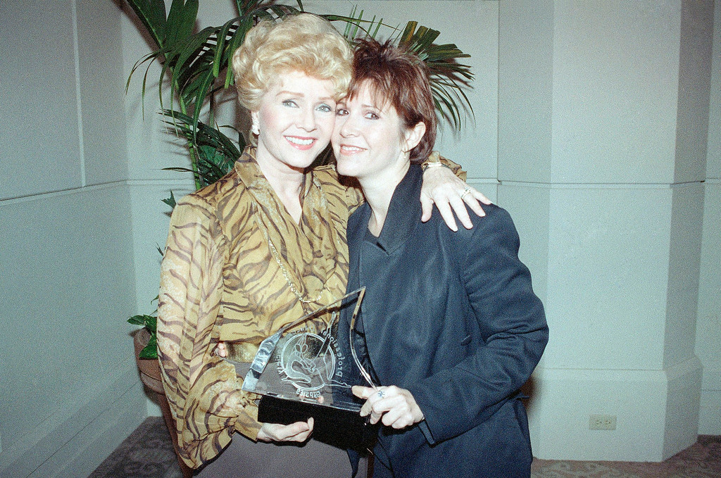 . Debbie Reynolds, left, poses for pictures with her daughter, Carrie Fisher, right, and the award given to her at the fifth annual Gypsy Awards, held at the Beverly Hilton Hotel in Beverly Hills, Calif., Feb. 4, 1991. Previous recipients include, Sammy Davis Jr. and Hermes Pan. (AP Photo/Mark J. Terrill)