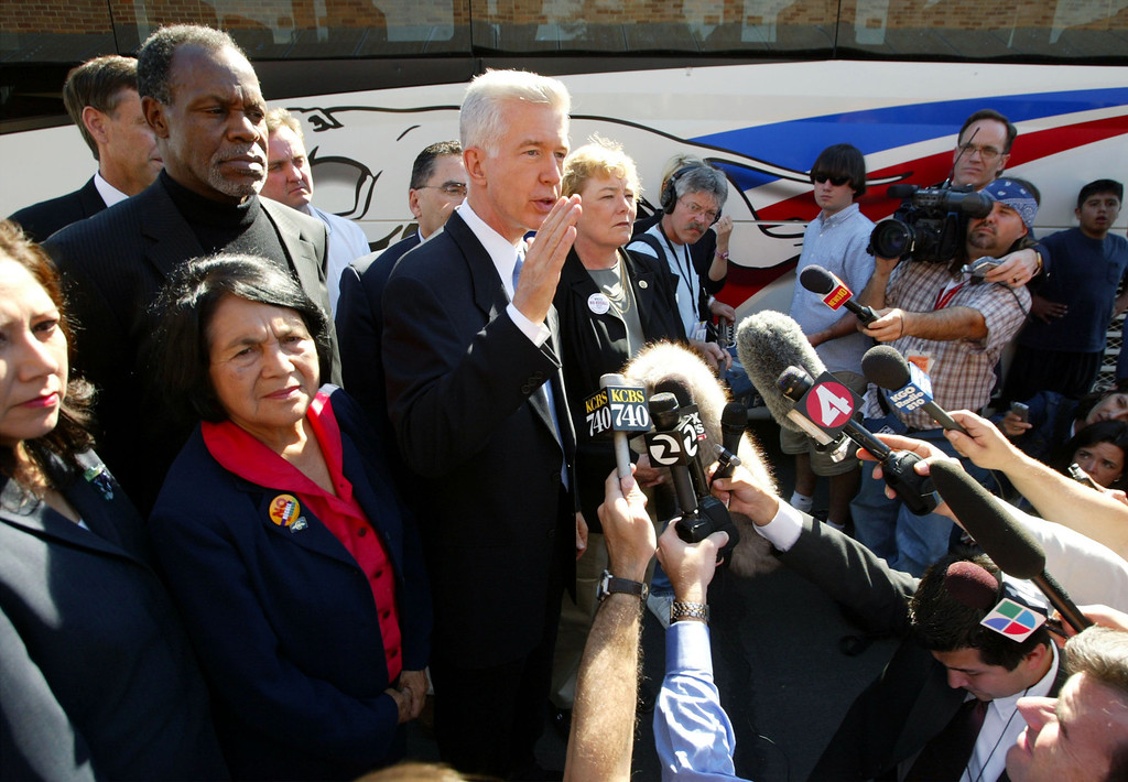 """. SAN JOSE, CA - OCTOBER 5:  California Gov. Gray Davis makes a statement to the press regarding sexual harassment allegations against candidate Arnold Schwarzenegger, with actor Danny Glover (Top L) and Dolores Huerta (Bottom L), co-founder of the United Farm Workers union, at his side as he arrives at a campaign stop at the International Brotherhood of Electrical Workers October 5, 2003 in San Jose, California. Davis is on a three-day \""""Just Say No Fly Around\"""" tour of the state to campaign in the final days before the October 7 special gubernatorial recall election.  (Photo by David McNew/Getty Images)"""