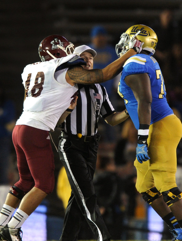 . New Mexico State\'s Kalei Auelua throws a punch at UCLA\'s Caleb Benenoch and is called for a foul in the fourth quarter, Saturday, September 21, 2013, at the Rose Bowl. (Photo by Michael Owen Baker/L.A. Daily News)