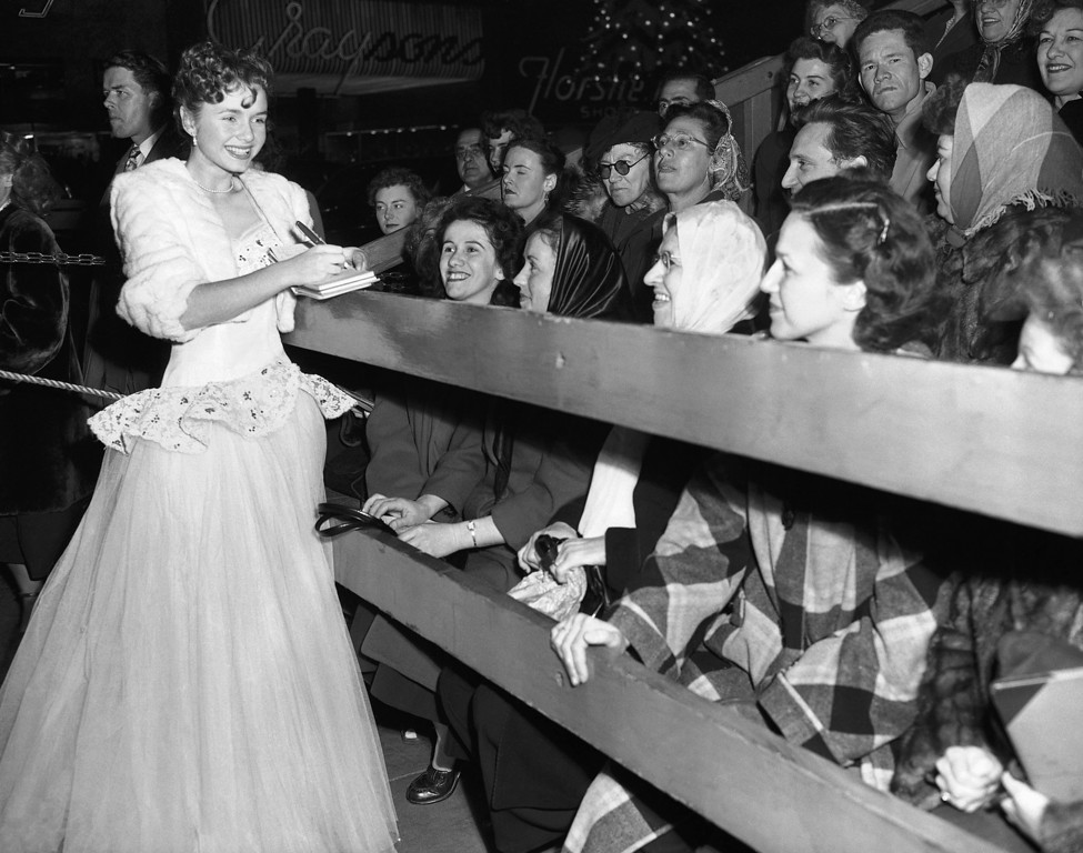 ". The curb show, for the fans who line up to get a glimpse, and perhaps an autograph, of the movie stars, is a part of any movie premiere in Hollywood, Los Angeles, California on Dec. 19, 1949. ""The Hasty Heart\"" opened on a chilly evening at Warner\'s Hollywood, but the curb show went on. Here Debbie Reynolds, one of the movie capital\'s young actresses, gives her autograph to some of the outside audience. (AP Photo/Frank Filan)"