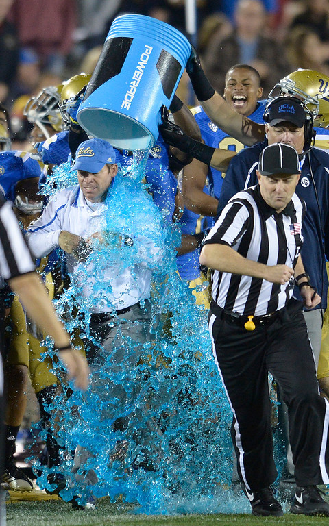 . UCLA Coach Jim Mora has a cooler of sports drink dumped on him in the final moments of the game. UCLA defeated USC 35 to 14 in a matchup of cross town rivals at the Los Angeles Memorial Coliseum in Los Angeles, CA.  photo by (John McCoy/Los Angeles Daily News)