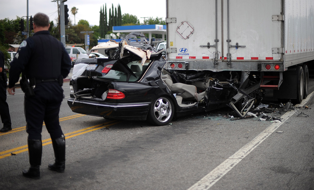 . Los Angeles Police investigate the scene of a traffic collision at the intersection of Topanga Canyon Blvd and Victory Blvd in Woodland Hills Monday, June 24, 2013. It took Los Angeles Fire Department personnel 31 minutes to extricate 2 females trapped in their vehicle lodged under a big rig loaded with tires. Both women were transported to trauma center in critical condition.  (Hans Gutknecht/Los Angeles Daily News)