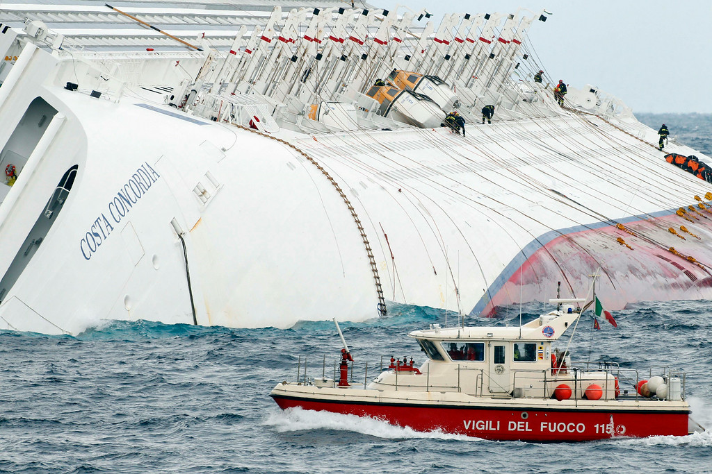 . Italian firefighters work on the hull of the grounded cruise ship Costa Concordia off the Tuscan island of Giglio, Italy, Thursday, Feb. 2, 2012. Bad weather conditions forced the temporary suspension of the recovery operation of the capsized cruise ship Costa Concordia. The ship contains about 500,000 gallons (2,400 tons) of heavy fuel and other pollutants, and fears are growing that those pollutants could spill out, damaging a pristine environment that is home to dolphins, whales and other marine life. (AP Photo/Pier Paolo Cito)