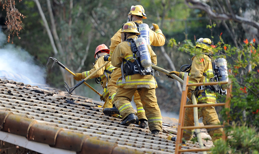 . Los Angeles County Firefighters vent a roof of a single family home that was damaged by a fire. The fire started in the garage along the 1300 block of Via Verde. No injuries, but 5 cars were destroyed including two jaguars in San Dimas, Calif., on Saturday, Jan.4, 2014.   (Keith Birmingham Pasadena Star-News)