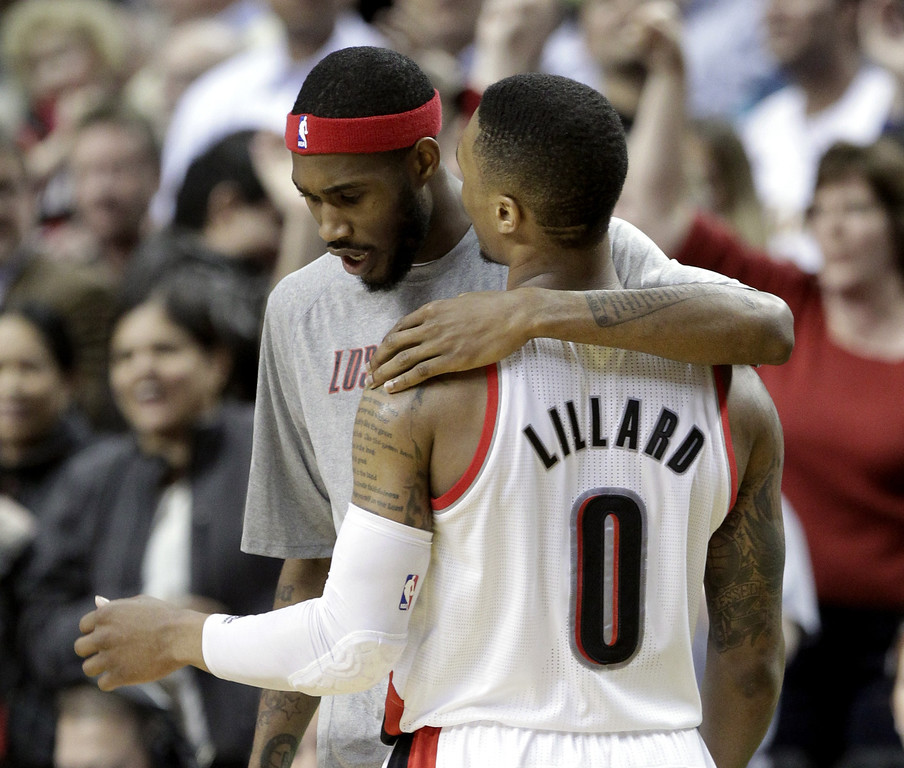 . Portland Trail Blazers guard Will Barton, left, puts his arm around teammate Damian Lillard as they walk off the court during the second half of an NBA basketball game in Portland, Ore., Monday, March 3, 2014.  Lillard scored 20 points and missed a three point shot in the final seconds as the Lakers won 107-106. (AP Photo/Don Ryan)
